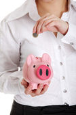 Woman putting euro coin in piggy bank. — Stock Photo