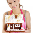 Royalty-Free Stock Photo: Young woman holding gingerbread house model