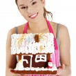 Young woman holding gingerbread house model — Stock Photo