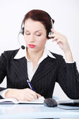Writng businesswoman in headset. — Stock Photo