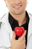 Doctor holding heart shape toy — Stock Photo