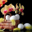 Foto de Stock  : Easter, eggs and spring yellow orchid with drop of dew