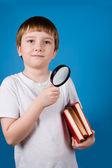 Jongen met vergrootglas glassa en stapel boeken — Stockfoto