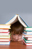 Boy hid behind the books — Stock Photo