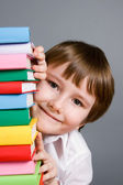 Boy looks out from a stack of books — Stock Photo