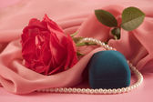 Red rose, beads and box for jeweller ornaments — Stock Photo