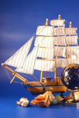 Sailing vessel, sea shells and the globe on a dark blue backgrou — Stock Photo