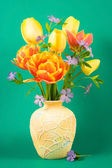 Vase with bouquet of tulips on a green background. — Stock Photo
