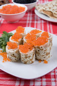Rolls from pancakes with red caviar on a plate — Stock Photo