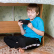 Boy sits under a table — Stock Photo