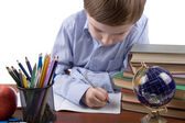 Serious boy writes in a notebook — Stock Photo