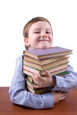 Happy boy hugging a pile of books — Stock Photo