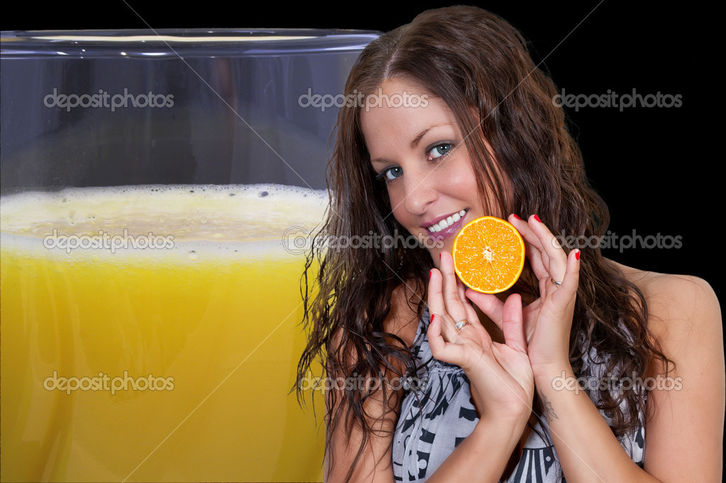 Beautiful woman holding an orange next to a glass of orange juice  Stock Photo #10228145