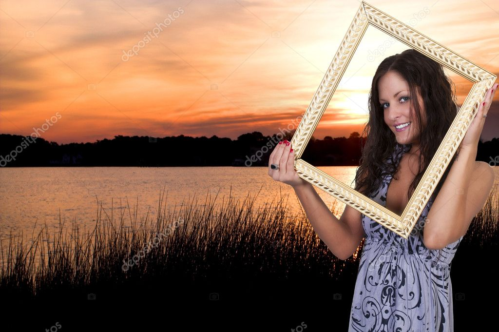 Beautiful woman looking through an ornate picture frame at the beach — Stock Photo #10228147