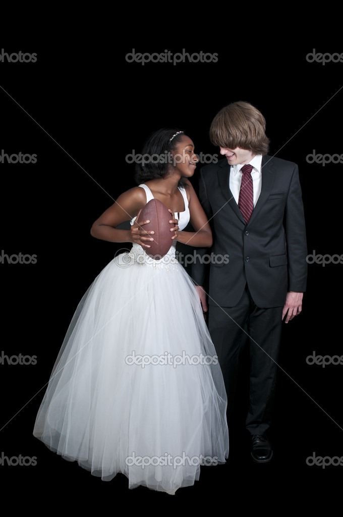 Caucasian man and a black African American woman newly married newlyweds with a football — Stock Photo #8323921