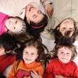 Children group in circle laying on ground — Stock Photo