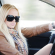 Beautiful blonde girl in her car — Stock Photo