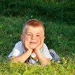Happy little boy laying on the grass in nature looking at camera — Stockfoto