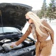 Blonde girl trying to fix her broken car — Stock Photo