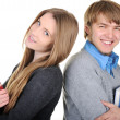 Royalty-Free Stock Photo: Young male and female students holding books and standing back to back