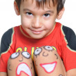 Cute little boy with painted smileys on his legs — Stockfoto