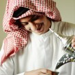 Stock Photo: Arabic young man pouring a traditional coffee