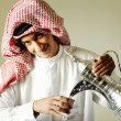 Arabic young man pouring a traditional coffee - Stok fotoğraf