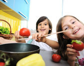 Little girl and boy cooking in the kitchen — Stock Photo