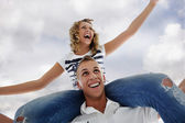 Portrait of teenage couple piggybacking isolated in white — Stock Photo