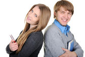 Young male and female students holding books and standing back to back — Stock Photo