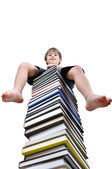 Little boy sitting on large stack of books — Stock Photo