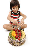 Kid eating fruit cake — Stock Photo