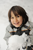 Cute little kid holding snowball — Stockfoto