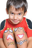 Cute little boy with painted smileys on his legs — Stock Photo