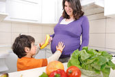 Pregnant woman with her son in kitchen — Stock Photo