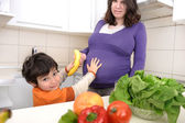 Pregnant woman with her boy in kitchen — Stock Photo