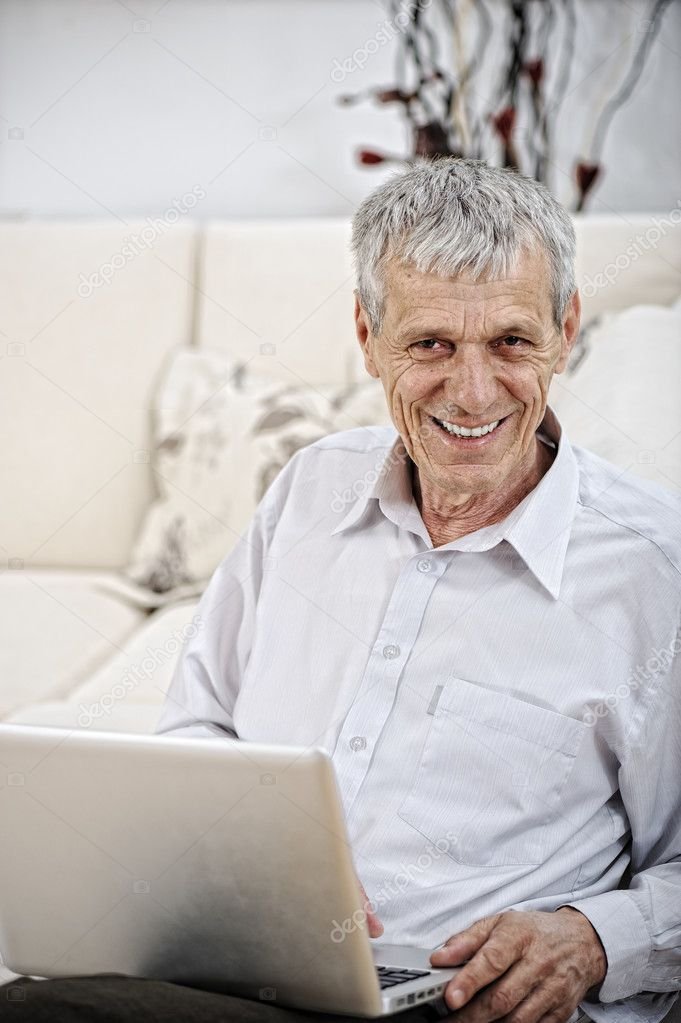 Senior Man Using Laptop Relaxing On Sofa At Home  Stock Photo #10418546