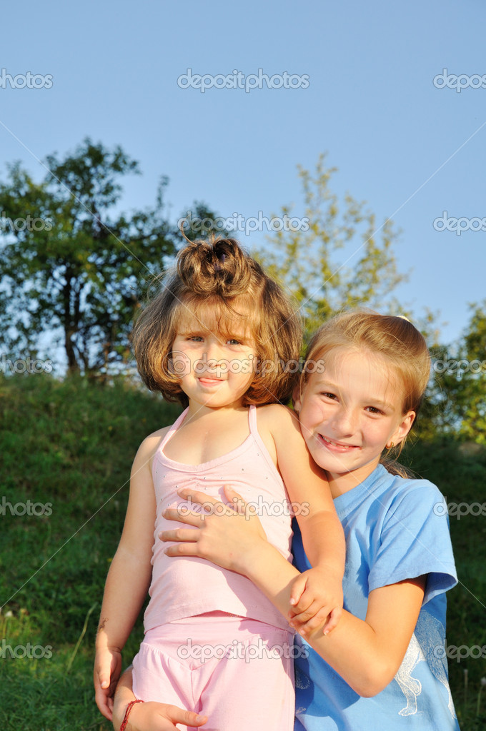 Two little girls standing together in the park, one holds another — Stock Photo #10418748