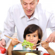 Grandfather and little boy in kitchen cooking together — Stock Photo