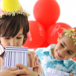 Birthday party, happy children celebrating, balloons and presents around - Stock Photo