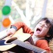 Stock Photo: Kid singing and playing guitar at home