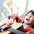 Little boy playing guitar at home — Stock Photo #10420770