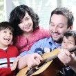 Happy family playing guitar together at home — Stock Photo #10420822