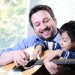 Father and son playing guitar at home — Stock Photo #10420850