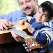 Father and son playing guitar at home - Stock Photo