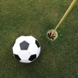 Football big ball at golf field hole — Photo