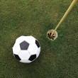 Football big ball at golf field hole — Foto de Stock