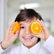 Little boy playing with orange slices on eyes as glasses — Stock Photo #10421107