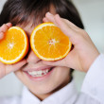 Little kid hplaying with fresh orange fruits — Stock Photo #10421111