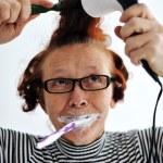 Senior woman brushing teeth and drying hair — Stock Photo #10421176